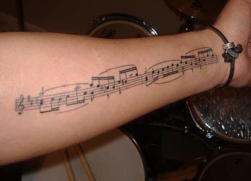 tatuajes de letras musicales en el brazo