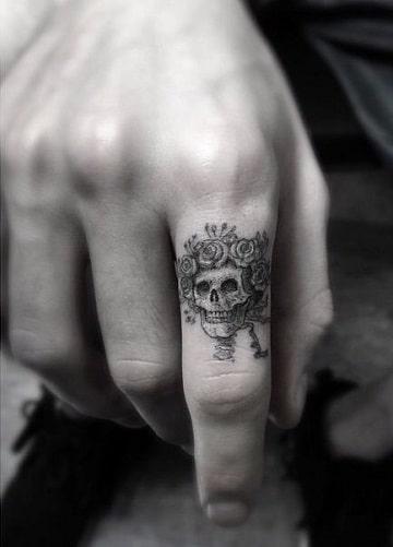 tatuajes de craneos con rosas en el dedo