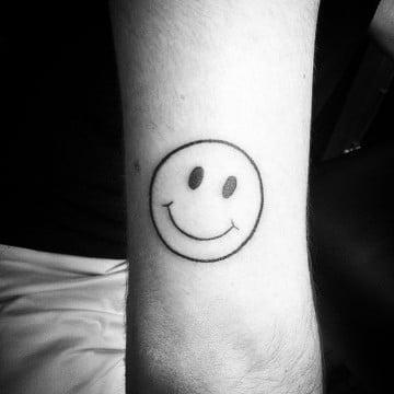 tatuajes de caritas felices en el brazo