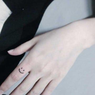 tatuajes de caritas felices en el dedo