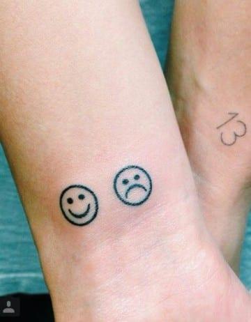 tatuajes de caritas tristes y alegres en la pierna