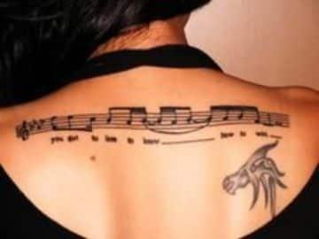 tatuajes de pentagramas musicales en espalda de mujer