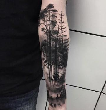 tatuajes de bosques en el antebrazo con lobo