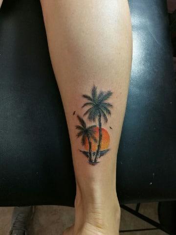 tatuajes de palmeras y playa en la pierna