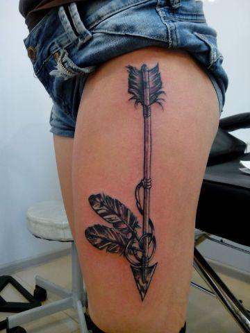 tatuajes de flechas y plumas en la pierna