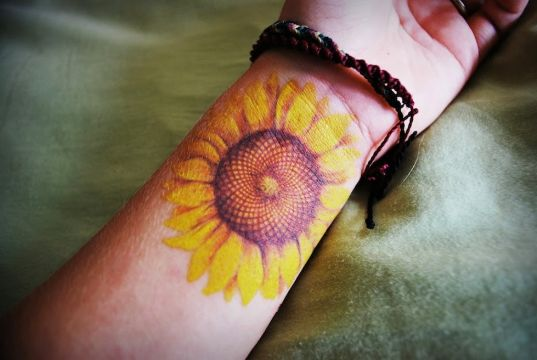 tatuajes de girasoles en la muñeca coloridos