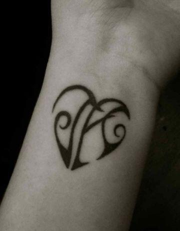 tatuajes de iniciales en la muñeca formando un corazon