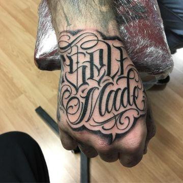 tatuajes de letras en la mano en el dorso
