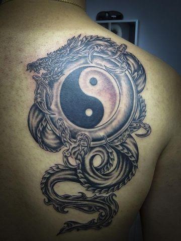 tatuajes de yin yang con dragon en omoplatos