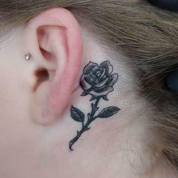 tatuaje rosa detras de la oreja con tallo y espinas